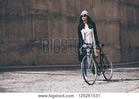 The perfect way to get anywhere. Beautiful young woman rolling her bicycle and looking away while walking outdoors