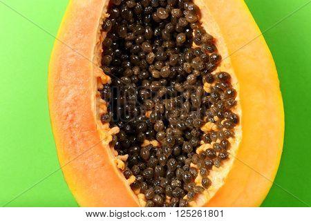 Halved papaya on green background