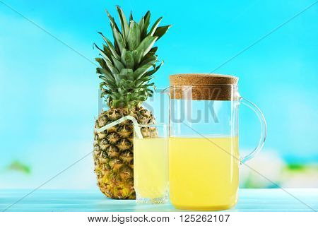 Ripe pineapple and juice in glassware on blue blurred background