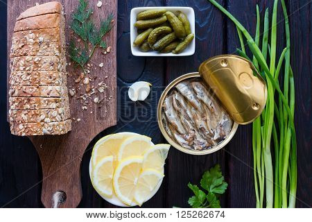 Bread With Grains, Pickled Gherkins, Lemon And Sprats On A Black Background