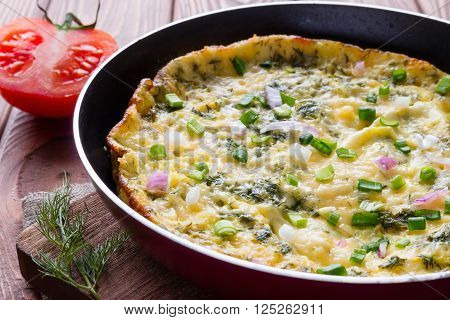 Delicious Omelette In A Frying Pan On A Wooden Background