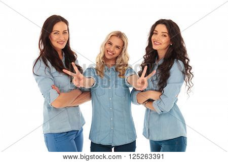 laughing blonde woman making the victory or peace sign while her friends are standing with hands crossed and smile on white background