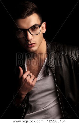 closeup portrait of sexy man in black leather jacket and glasses, pulling his white shirt while looking at the camera in isolated black studio background