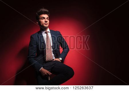 young businessman in black suit with red tie posing seated with hand in pocket and legs crossed while looking away from the camera in red studio background