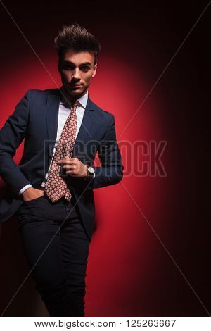 confident young businessman in black suit with red tie posing standing with hand in pocket and legs crossed while arranging his tie in red studio background. he is looking at the camera.