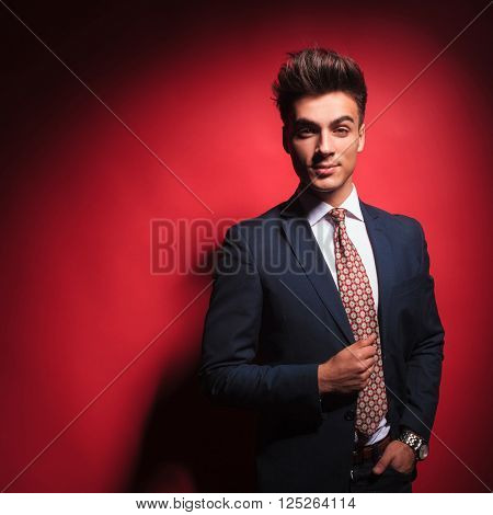 portrait of attractive young businessman in black suit with red tie, posing with hand in pocket, arranging his jacket, in red studio background while looking at the camera