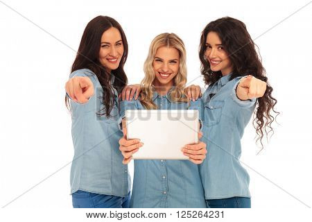 three casual women holding a tablet pad computer pointing their fingers to you, on white studio background