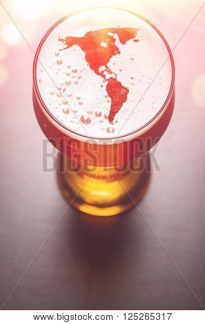 American beer concept, America silhouette on foam in beer glass on black table, view from above