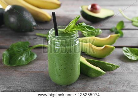 Fresh avocado smoothie with slices on wooden background