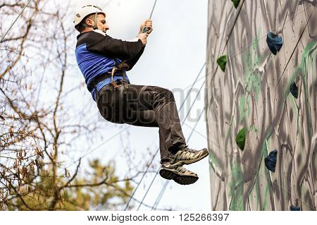 Man Climbing Up A Wall In An Exercise For Mountaineering