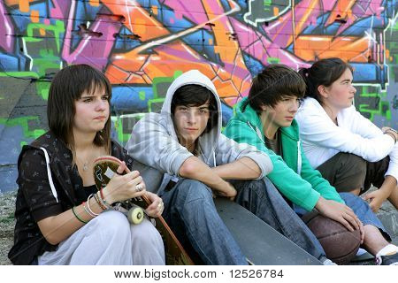Group of teenagers in front of graffiti