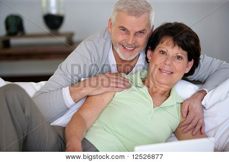 Portrait of senior couple sitting in sofa