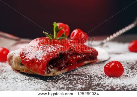 Powdered cherry strudel with mint on dark red background