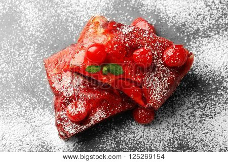 Powdered cherry strudel with mint, closeup