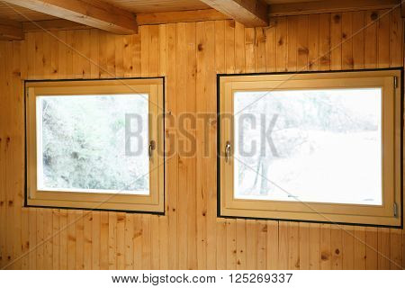 New efficient three pane wooden windows installed in an old wooden house replacing wasteful old windows. Home renovation sustainable living energy efficiency concept.