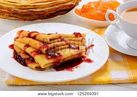 Pancakes with jam and cup of tea.