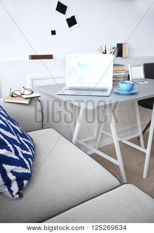 Modern interior. Comfortable workplace. Table with laptop and cup of coffee on it