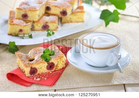 Delicious piece of cherry cake with a fresh cup of cappuccino