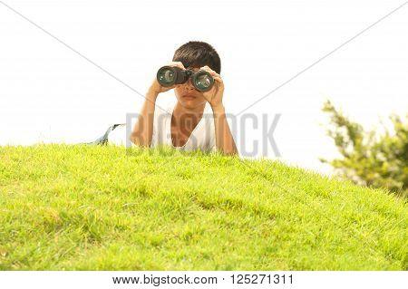Asian young boy lying on mound seeking Binoculars.