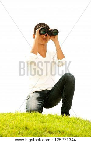 Asian young boy sit on mound seeking Binoculars.