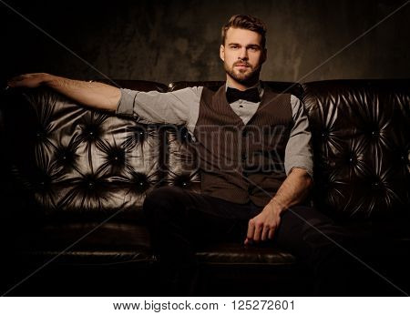 Young handsome old-fashioned bearded man sitting on comfortable leather sofa on dark background.