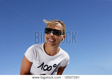 Smiling woman with mp3 walkman and sunglasses