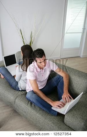 Portrait of a man and a woman sat on a sofa back to back in front of a laptop computer