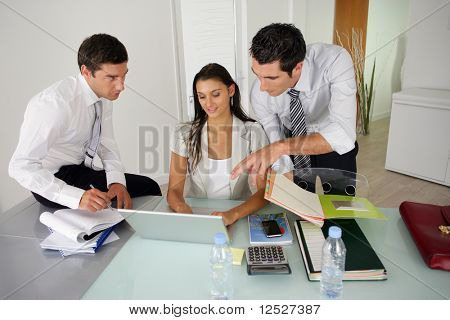 A woman and two men watching a laptop computer in an office