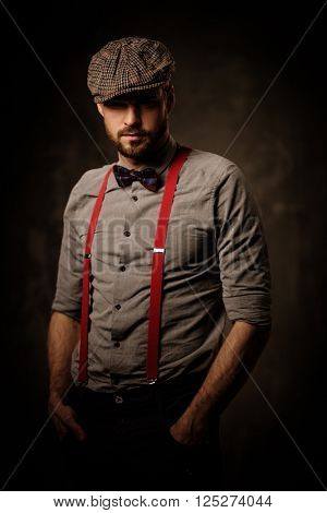 Serious old-fashioned man in tweed hat wearing suspenders and bow tie, posing on dark background.