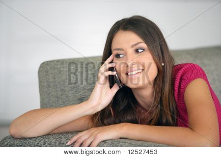 Portrait of a smiling woman sat on a sofa phoning with a cell phone