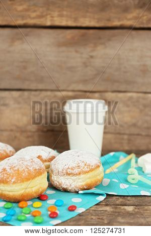 Delicious sugary donuts with blue napkin on wooden background