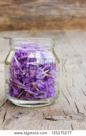 pale lilac flower petals in a glass jar on old wooden boards in the cracks. the concept of aromatherapy alternative medicine