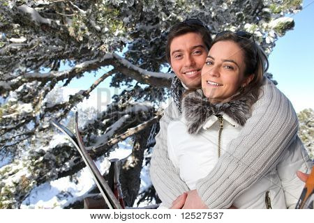 Portrait of  smiling man and woman embracing at the snow