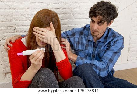 young couple with boyfriend comforting depressed and worried pregnant gir holding positive result pregnancy test