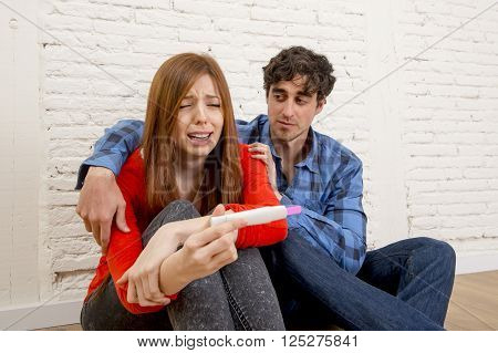 boyfriend comforting pregant girl crying and holding positive result pregnancy test in unwanted baby concept