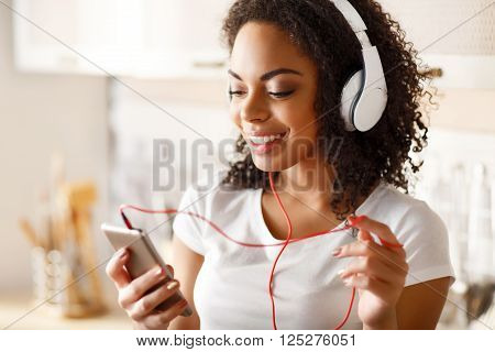 Rise your spirit. Positive smiling enjoyable girl holding cell phone and listening to music while  expressing gladness