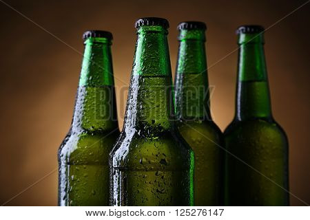 Four green glass bottles of beer on dark lighted background, close up