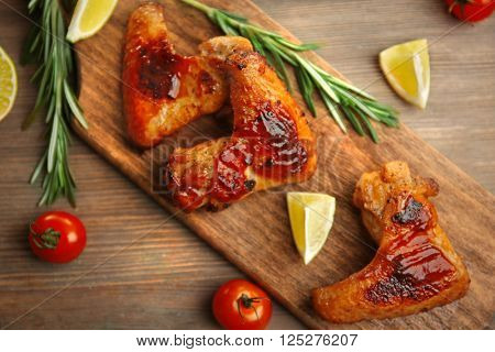 Grilled chicken wings with garden-stuff and tomatoes on cutting board