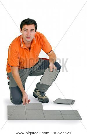 Tiler on the knees putting tiles with white background