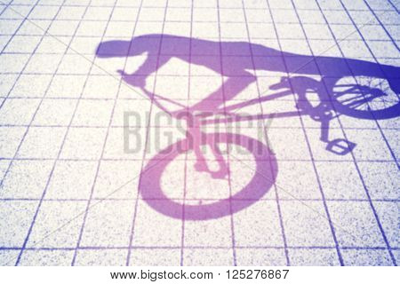 Retro toned blurred shadow of a teenager riding a bmx bike.