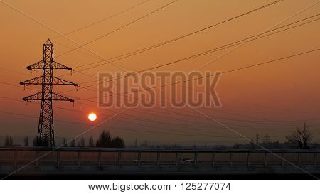 Electrical transmission tower Energy transport road transport. Against Sunset