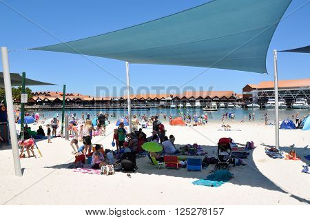 HILLARYS,WA,AUSTRALIA-JANUARY 22,2016: Beach recreation with families and shade sails in the swimming cove at Hillarys Boat Harbour, in Hillarys, Western Australia.