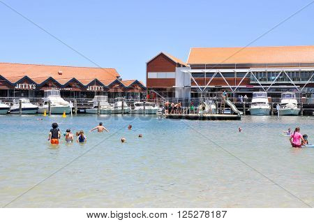 HILLARYS,WA,AUSTRALIA-JANUARY 22,2016: Swimming cove with families, yachts and pontoon at Hillarys Boat Harbour, in Hillarys, Western Australia.