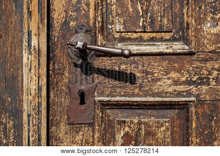 Beautiful old metal door handle with hand on an antique wooden door.