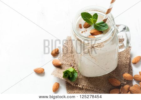 Shake from almond milk banana and coconut in a mason mug. White background with copy space.