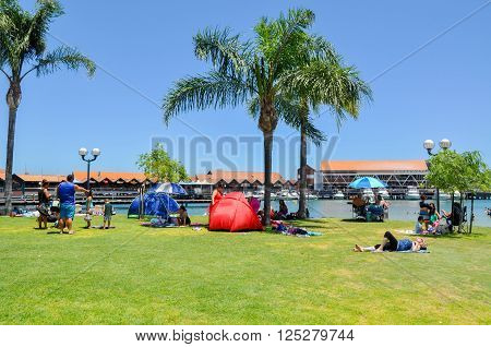 HILLARYS,WA,AUSTRALIA-JANUARY 22,2016: Foreshore with tourists and tropical palm trees at Hillarys Boat Harbour in Hillarys, Western Australia.