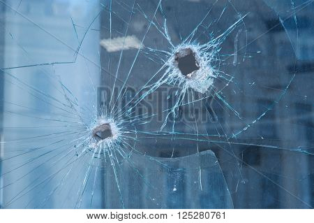 two bullet holes in the glass windows.