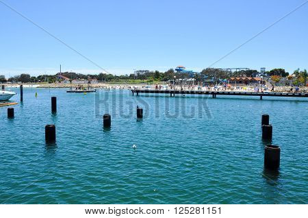 HILLARYS,WA,AUSTRALIA-JANUARY 22,2016: Swimming cove jetty, beach, ocean pilings and tourists at Hillarys Boat Harbour in Hillarys, Western Australia.