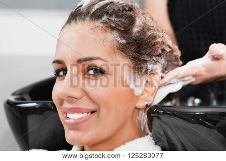 Hair salon - washing hair, female looking at camera
