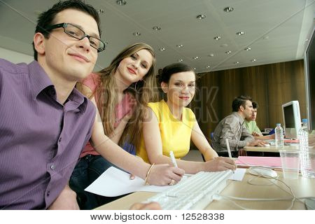 Smiling man and women in front of a laptop computer